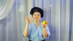 Повар женщины в улыбках рисбермы, держит желтый перец в ее руке и показывает ОК с ее рукой акции видеоматериалы