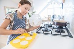 Повар маленькой девочки в кухне стоковая фотография