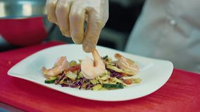 Повар украшает салат с креветками