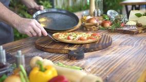 Повар шеф-повара подготовил пиццу с томатами, pepperoni и сыром в пиццерии Горячая сваренная итальянская пицца на деревянном стол сток-видео