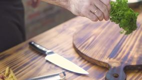 Повар шеф-повара принимая свежую петрушку и режа с ножом на деревянной доске Сварите прерывать зеленую петрушку на разделочной до акции видеоматериалы