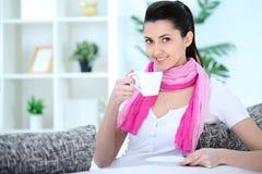 Повелительница красотки сидя на софе и выпивая кофе стоковое фото