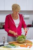 повелительница кухни делая детенышей салата стоковые изображения