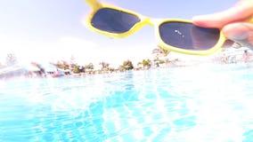 Поверхность воды бассейна и человека бросая прочь солнечные очки сток-видео