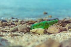Поверхность зеленой бутылки на пляже стоковое фото