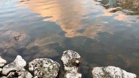 Поверхность и утесы озера на заходе солнца акции видеоматериалы