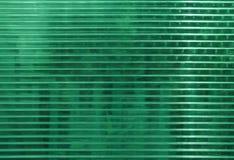 Поверхность поликарбоната с зелеными объектами позади Стоковые Фото