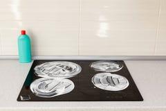 Поверхность плиты индукции покрыта с тензидом Чистка дома - пластичные бутылки с тензидами на таблетке кухни Стоковая Фотография
