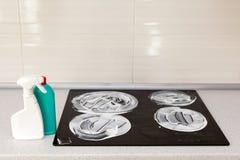 Поверхность плиты индукции покрыта с тензидом Чистка дома - пластичные бутылки с тензидами на таблетке кухни Стоковое фото RF
