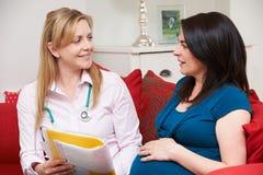 Повитуха обсуждая медицинские примечания с беременной женщиной Стоковое Фото