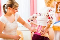 Повитуха связывая беременную женщину тесьмой с Kinesio-лентой стоковая фотография rf