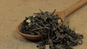 Поворачивать ложку, переполняющ при чай лист зеленый, лежа на мешковине видеоматериал