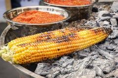 Поворачивают зажаренную мексиканскую мозоль с красным перцем на горячие угли Фаст-фуд на улице стоковое изображение rf