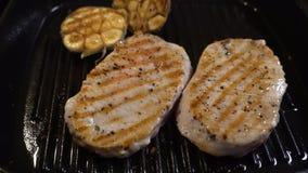 Поворачивая мясо в литом железе с концом чеснока акции видеоматериалы