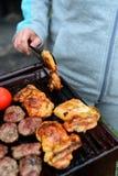 Поворачивая цыпленок с схватом на барбекю Стоковые Изображения