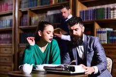 поворотливая концепция дела и грамматики Пары в библиотеке с кофе машинки и чайника выпивая от чашки словесность стоковая фотография