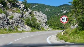 Поворот дороги с знаком ограничения в скорости от взгляда водителей Стоковое Фото