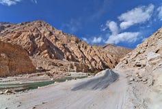 Поврежденная дорога вдоль реки в горах Стоковые Изображения