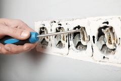 Поврежденные провода в электрическом выходе в стене Нарушение электрических правил техники безопасности стоковое изображение rf