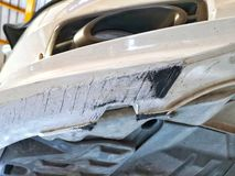 Поврежденный бампер автомобиля передний от выскабливать дороги стоковые изображения