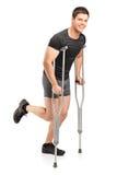 Поврежденный молодой мыжской спортсмен гуляя с костылями стоковое изображение