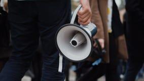 Повстанец идет на забастовку через толпу и владения в руке мегафон или громкоговоритель