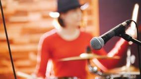 повторение Барабанщик девушки concentratedly играя барабанчики Mic в фокусе видеоматериал