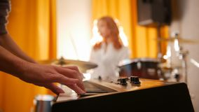 повторение Выразительный барабанщик девушки и парень на клавиатурах Фокус от рук к барабанчикам Backlight стоковые изображения rf