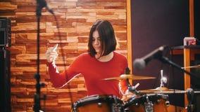 повторение Девушка в красном свитере запальчиво играет барабанчики видеоматериал