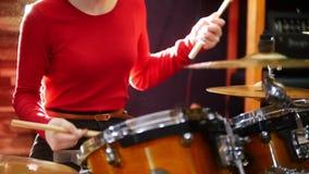повторение Девушка в красном свитере запальчиво играет барабанчики Яркое освещение акции видеоматериалы
