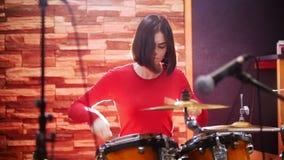 повторение Девушка в красном свитере запальчиво играет барабанчики акции видеоматериалы