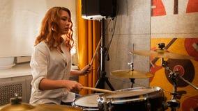 повторение Девушка имбиря играет на барабанчиках в студии Фокус на девушке стоковые изображения rf