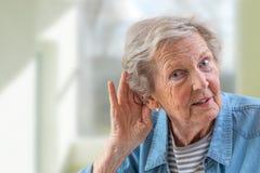 Повторение, пожалуйста Конец-вверх стороны очаровывать пожилую женщину держит руку ее ухом и борется для того чтобы услышать что- стоковая фотография rf