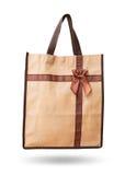 Повторное пользование коричневого цвета сумки подарка рециркулирует для того чтобы получить в ленте (смычке) изолированной дальше Стоковая Фотография
