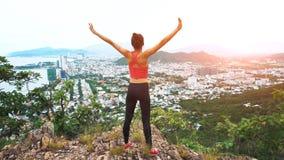 Повышение бегуна женщины вручает вверх в воздухе Женщина бежит na górze горы, веселя в выигрывая жесте стоковое фото rf