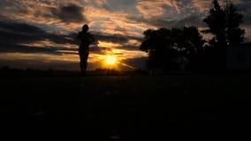 Повышение женщины подготовляет к небу на пляже во время захода солнца, замедленного движения акции видеоматериалы