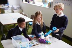 Повышенный взгляд 3 детей начальной школы стоя на таблице в классе, работая вместе с блоками конструкции игрушки стоковое фото rf