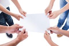 Повышенный взгляд семьи держа пустую бумагу Стоковые Изображения RF