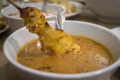 Погружение малайзийского цыпленка satay в очень вкусный соус арахиса, один из Стоковые Изображения
