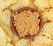 Погружение Hummus в шаре с близким взглядом картофельных стружек Стоковые Изображения RF