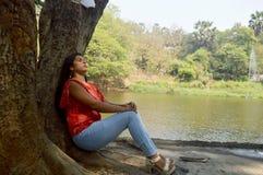 Подавленная девушка сидя около озера под деревом стоковая фотография