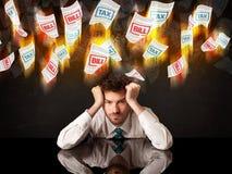 Подавленный бизнесмен сидя под горящими бумагами налога и счета Стоковое Изображение