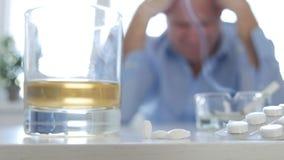 Подавленный и разочаровыванный человек после злоупотребления лекарств и алкоголя стоковое фото rf