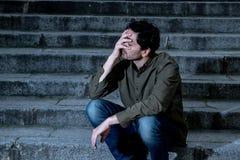 Подавленный человек сидя вне бортовое на шагах чувствуя утомлянный и унылый стоковое изображение rf