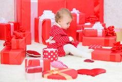 Подарки для рождества ребенка первого Маленькая игра младенца около кучи в оболочке красных подарочных коробок рождество сперва м стоковая фотография rf