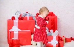 Подарки для рождества ребенка первого Немногое игра ребенка около кучи подарочных коробок Праздник семьи Деятельности при рождест стоковые изображения rf