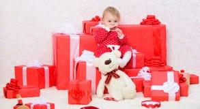Подарки для рождества ребенка первого Отпразднуйте первое рождество Немногое игра ребенка около кучи подарочных коробок Семья стоковое изображение