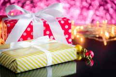подарки и игрушки на предпосылке стеклянного стола и красного света bokeh Стоковое Изображение RF