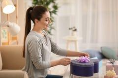 Подарки красивой молодой женщины пакуя дома стоковое изображение