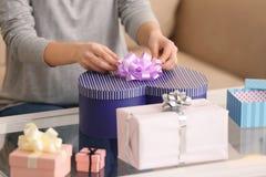 Подарки красивой молодой женщины пакуя дома стоковые фотографии rf
